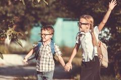 Glimlachende jonge schoolkinderen in een school eenvormig tegen een boom Stock Afbeeldingen