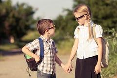 Glimlachende jonge schoolkinderen in een school eenvormig tegen een boom Royalty-vrije Stock Foto