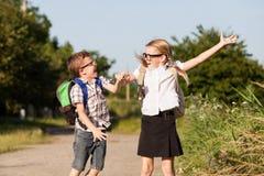 Glimlachende jonge schoolkinderen in een school eenvormig tegen een boom Royalty-vrije Stock Foto's