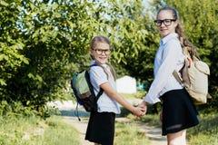 Glimlachende jonge schoolkinderen in een school eenvormige opnieuw status Stock Fotografie