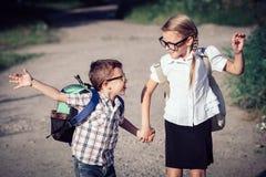 Glimlachende jonge schoolkinderen in school het eenvormige springen op Stock Afbeelding
