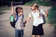 Glimlachende jonge schoolkinderen in school het eenvormige springen op Stock Foto's
