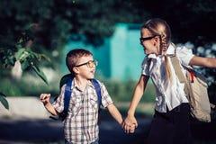 Glimlachende jonge schoolkinderen in school het eenvormige springen op Royalty-vrije Stock Afbeelding