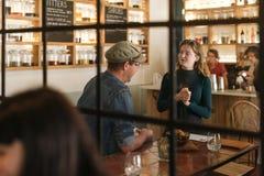 Glimlachende jonge serveerster die met een bistroklant spreken Stock Afbeeldingen