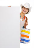 Glimlachende strandvrouw in hoed die leeg aanplakbord toont Stock Foto