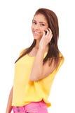 Glimlachende jonge toevallige vrouw die op telefoon spreekt Stock Foto
