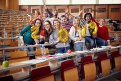 Glimlachende jonge vrienden die partij op universiteit hebben royalty-vrije stock foto