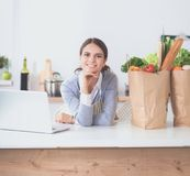 Glimlachende jonge vrouw in de keuken dichtbij bureau Stock Afbeeldingen