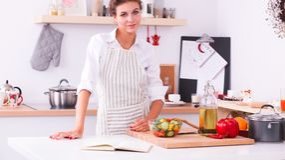 Glimlachende jonge vrouw in de keuken, op Kerstmisachtergrond Royalty-vrije Stock Foto's