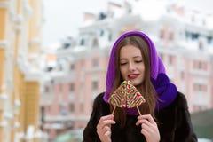 Glimlachende jonge vrouw in de winterkleren die met smakelijke kleurrijk stellen Stock Foto