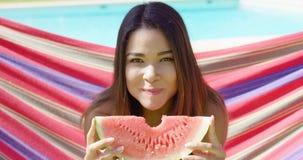 Glimlachende jonge vrouw die één watermeloenplak houden stock footage