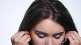 Glimlachende jonge vrouw die aan muziek met oortelefoons luisteren die op witte achtergrond wordt geïsoleerd stock videobeelden