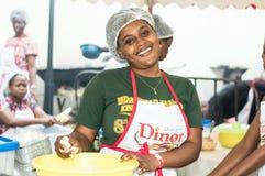 Glimlachende jonge vrouw die attiéké dienen Royalty-vrije Stock Foto's