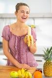 Glimlachende jonge vrouw die banaan in keuken eten Stock Afbeelding