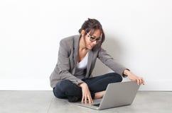 Glimlachende jonge vrouw die bij computer het ontspannen op de vloer werken stock afbeeldingen