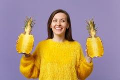 Glimlachende jonge vrouw die in bontsweater opzij houdend halfs van vers rijp ananasfruit op violette pastelkleur geïsoleerd kijk royalty-vrije stock afbeeldingen