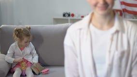 Glimlachende jonge vrouw die camera, het leuke meisje spelen achter bank, alleenstaande ouder kijken stock footage
