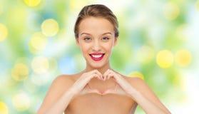 Glimlachende jonge vrouw die de handteken tonen van de hartvorm Royalty-vrije Stock Foto's