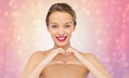 Glimlachende jonge vrouw die de handteken tonen van de hartvorm Stock Afbeeldingen