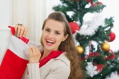 Glimlachende jonge vrouw die de sokken van Kerstmis controleert Stock Foto's