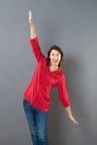 Glimlachende jonge vrouw die die wapens met behulp van wijd worden geopend om te vliegen stock afbeelding