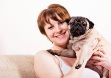 Glimlachende jonge vrouw die een hond in haar wapens houden Royalty-vrije Stock Foto