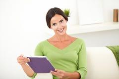 Glimlachende jonge vrouw die een tablet houden Stock Fotografie