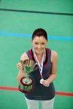 Glimlachende jonge vrouw die een trophee en een medaille houdt Stock Afbeelding