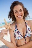 Glimlachende jonge vrouw die een zeester op het strand ontdekken Royalty-vrije Stock Foto's