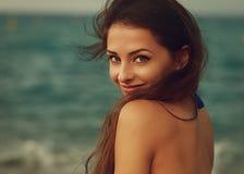Glimlachende jonge vrouw die gelukkig op overzees kijken royalty-vrije stock afbeeldingen