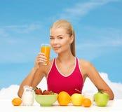 Glimlachende jonge vrouw die gezond ontbijt eten royalty-vrije stock afbeeldingen