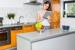Glimlachende jonge vrouw die het net in de keuken surfen Stock Foto