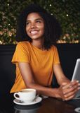 Glimlachende jonge vrouw die in koffie weg kijken stock foto