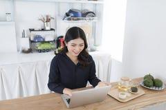 Glimlachende jonge vrouw die laptop in de keuken thuis met behulp van stock afbeelding