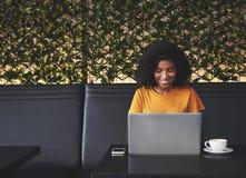 Glimlachende jonge vrouw die laptop in koffie met behulp van stock fotografie