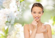 Glimlachende jonge vrouw die lippenpommade toepassen op haar lippen Royalty-vrije Stock Afbeeldingen
