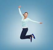 Glimlachende jonge vrouw die in lucht springen Royalty-vrije Stock Afbeeldingen