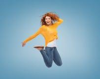 Glimlachende jonge vrouw die in lucht springen Stock Foto