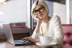 Glimlachende jonge vrouw die met laptop computer in koffie werken royalty-vrije stock afbeeldingen