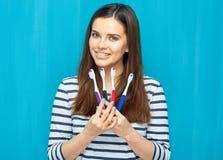 Glimlachende jonge vrouw die met tandsteunen toothy borstel kiezen stock afbeelding