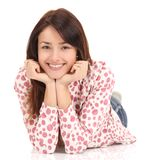 Glimlachende jonge vrouw die op de vloer liggen stock fotografie