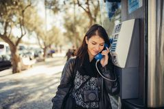 Glimlachende jonge vrouw die op haar smartphone op de straat spreken Communicerend met vrienden, vrije vraag en berichten voor jo royalty-vrije stock foto's