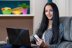 Glimlachende jonge vrouw die op laag en het gebruiken van laptop leggen stock afbeeldingen