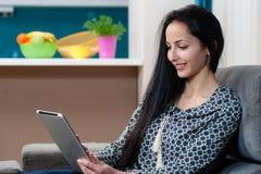Glimlachende jonge vrouw die op laag en het gebruiken van laptop leggen stock fotografie