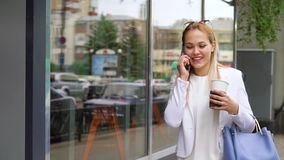 Glimlachende jonge vrouw die op straat lopen die op cel telefoon en het houden van koffie spreken stock footage