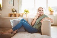 Glimlachende jonge vrouw die op telefoon op bank in woonkamer spreken royalty-vrije stock afbeelding
