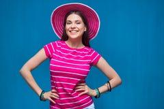 Glimlachende jonge vrouw die roze strandhoed dragen Stock Foto's