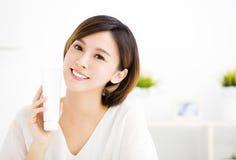 Glimlachende jonge vrouw die skincare producten tonen stock foto's