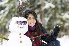 Glimlachende jonge vrouw die sneeuwman koesteren Stock Foto