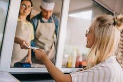 glimlachende jonge vrouw die in voedsel betalen stock foto